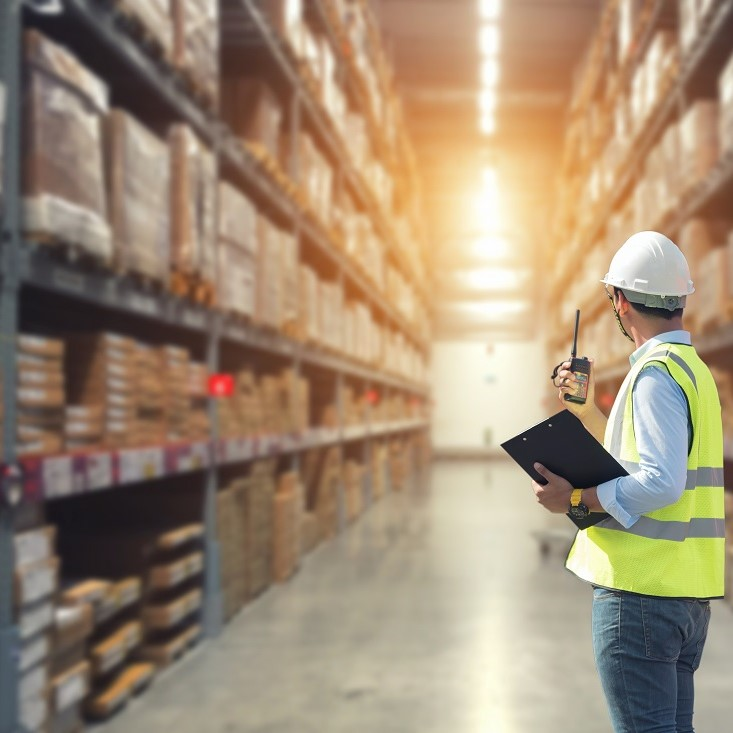 Warehouse worker talking on the phone holding clipboard in a large warehouse,logistics concept.